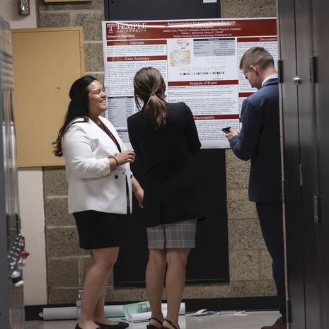 School of Pharmacy students discussing research poster