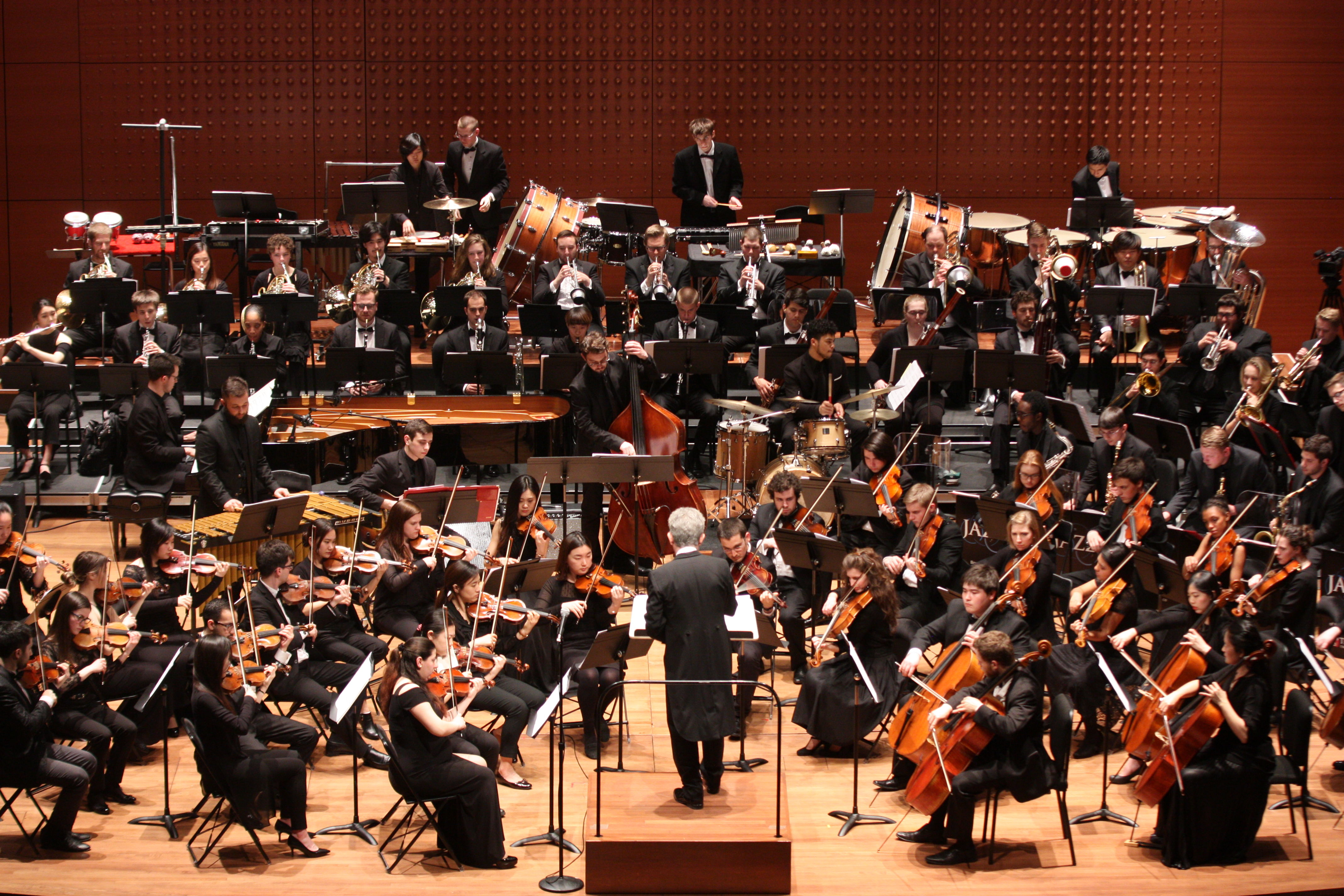 Temple University Symphony orchestra and jazz band musicians on stage at Lincoln Center, conducted by Andreas Delfs.