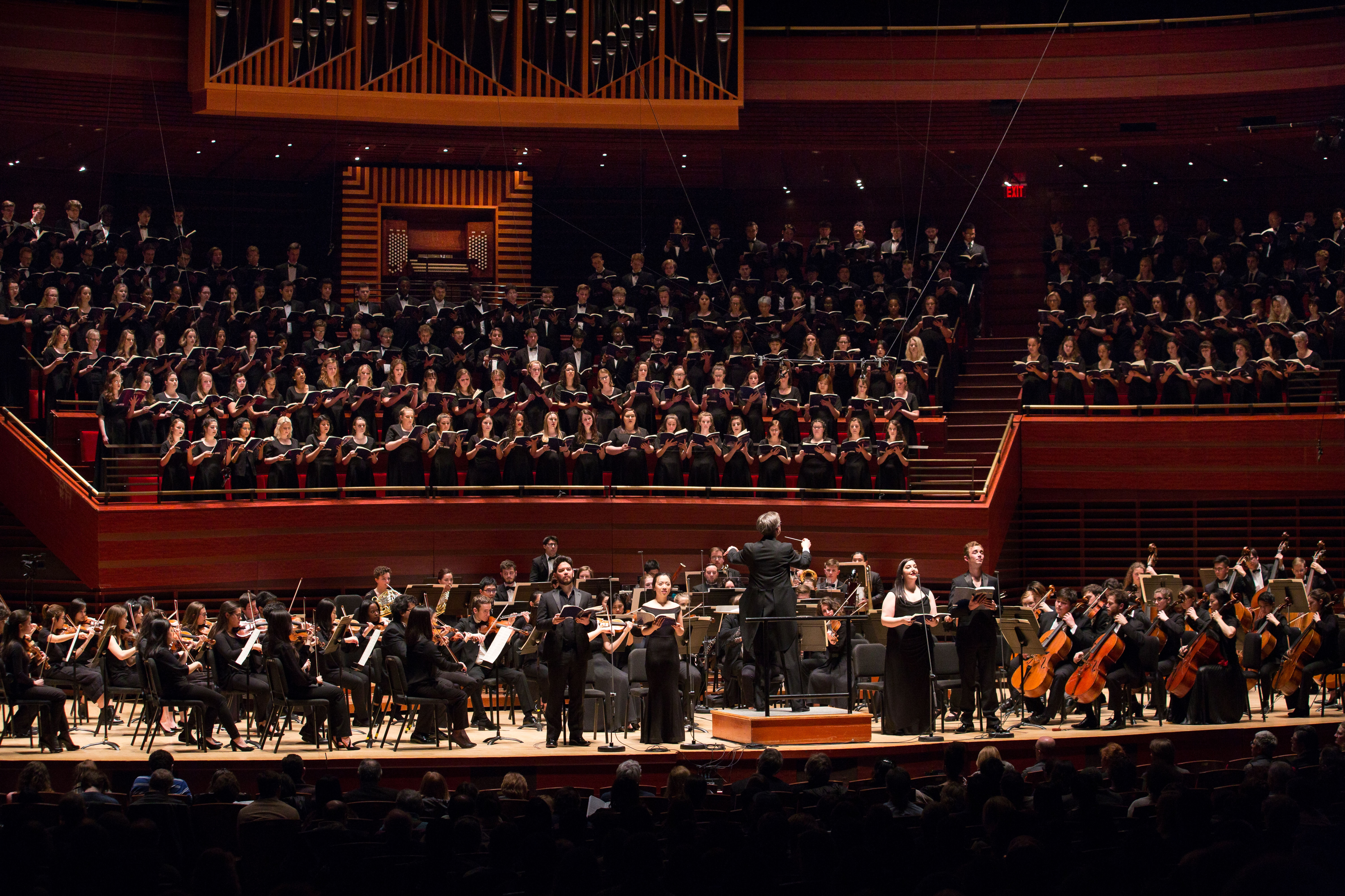 Choir and orchestra members on stage at the Kimmel Center for the Performing Arts, conducted by Paul Rardin.