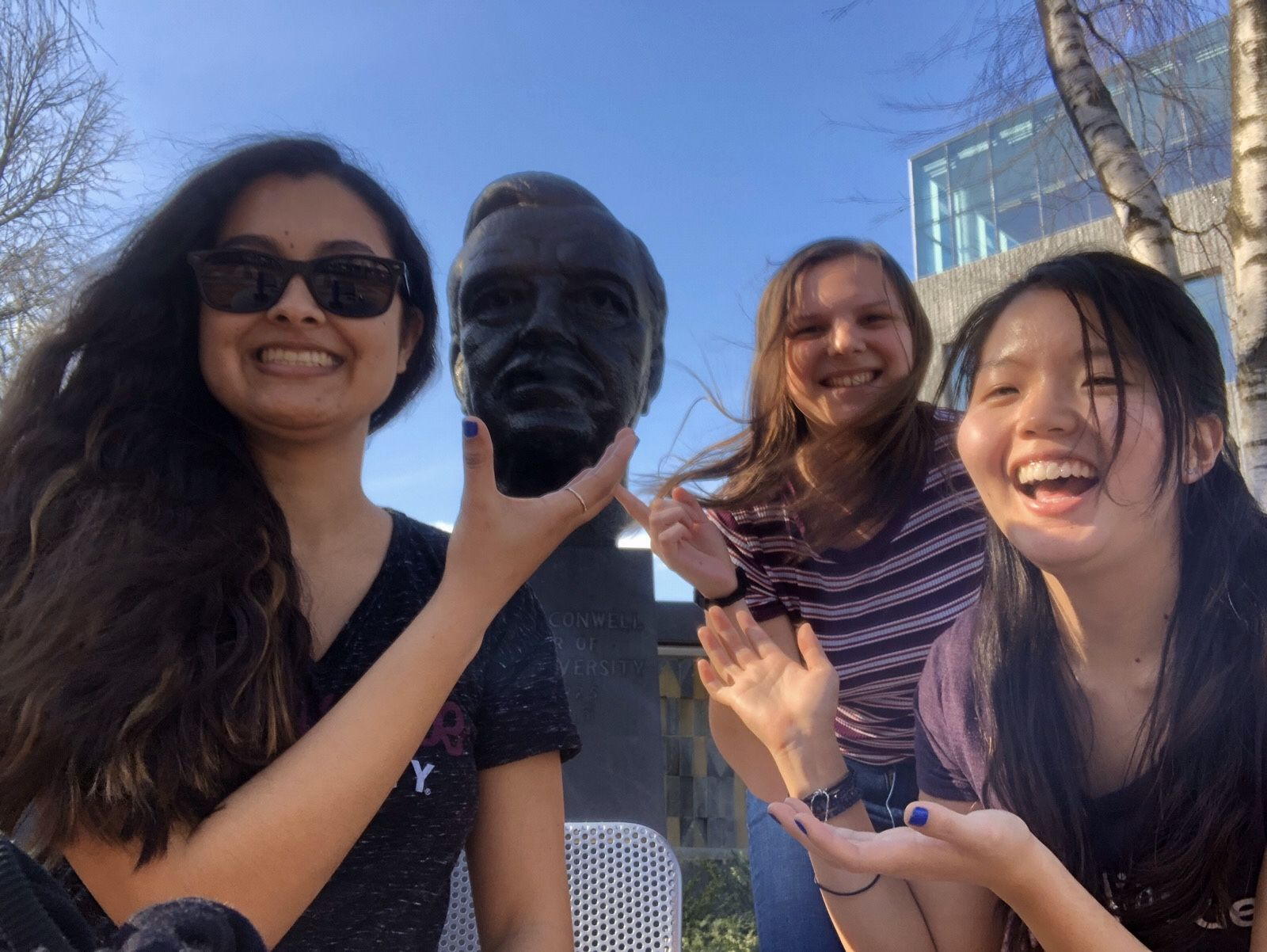 Students pose on campus with the Russell Conwell statue.