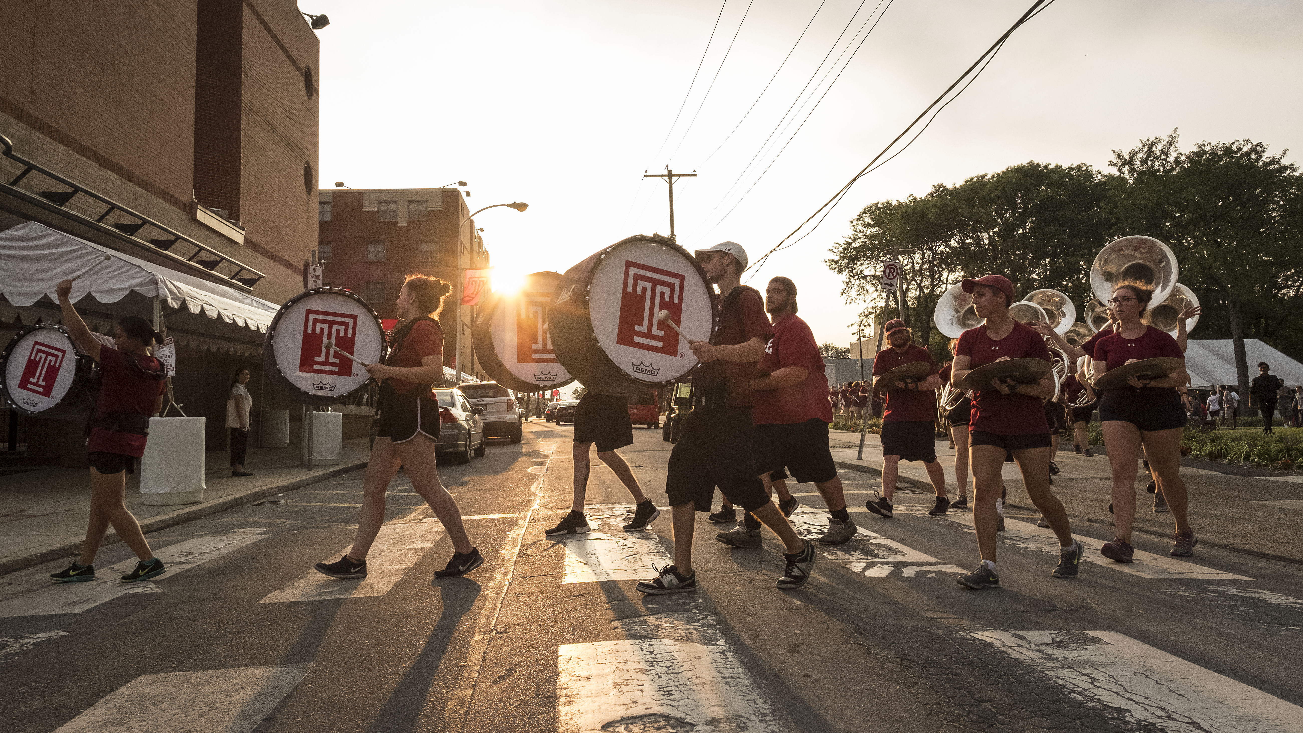 Temple marching band members perform as they walk across a street on Temple's campus during Welcome Week.