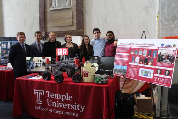 College of Engineering students pose at their table during a conference.