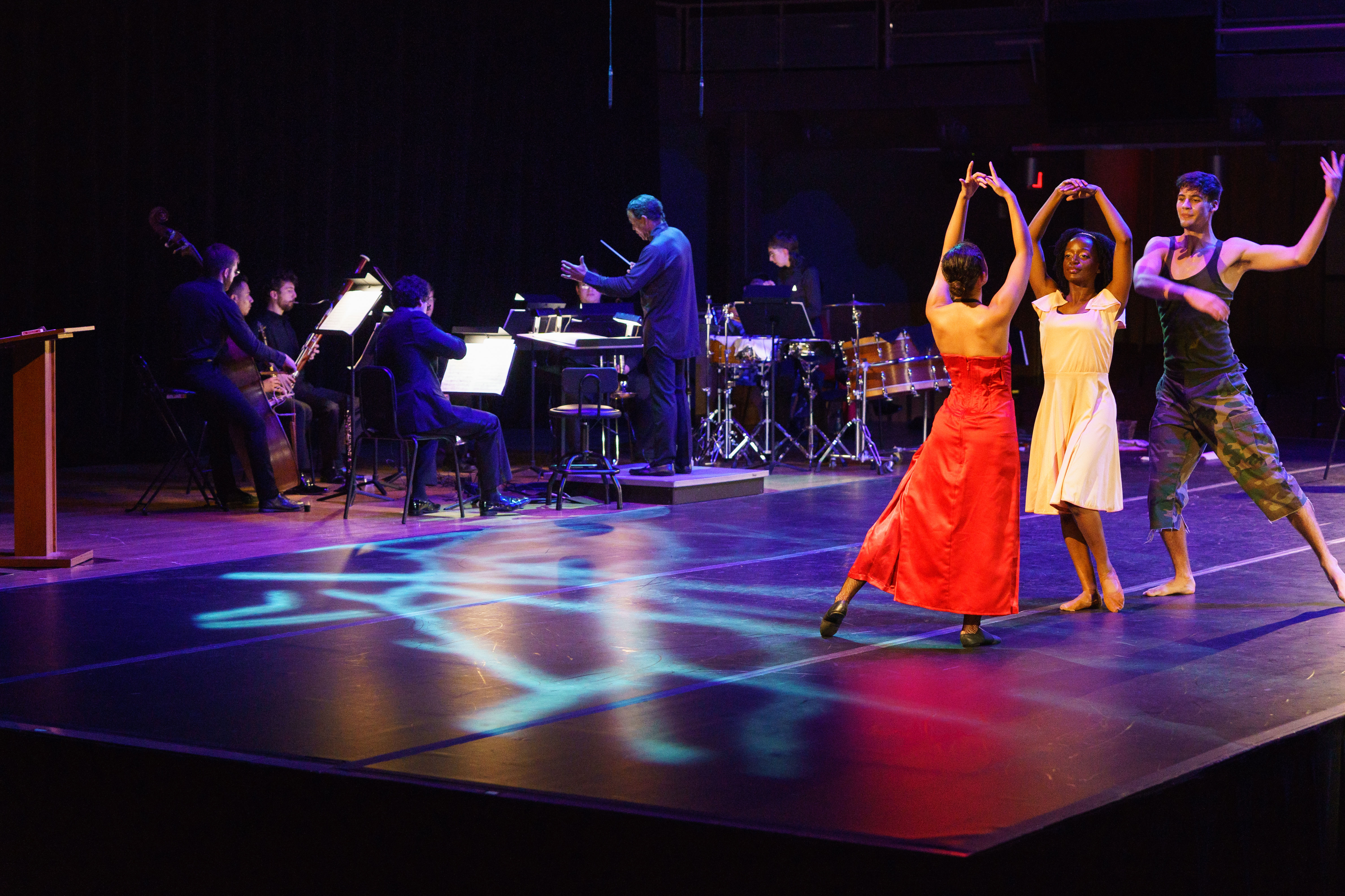 Temple students dance on stage with orchestra musicians and a conductor performing behind them at the Temple Performing Arts Center.