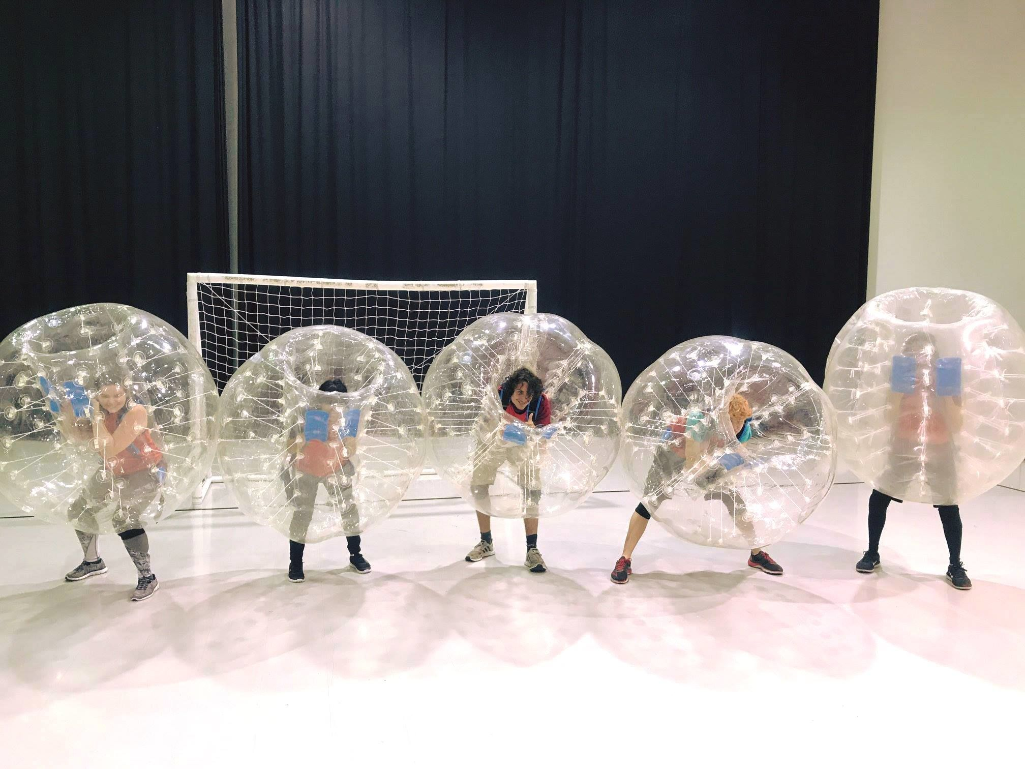 Five students at Temple University Japan stand inside large bubble balls.