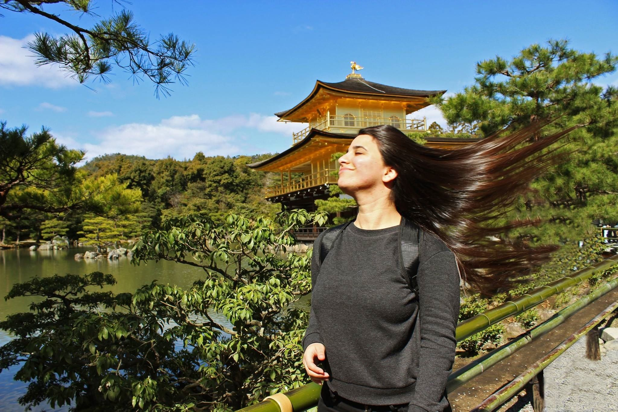 A Temple University Japan student poses in front of a traditional Japanese house.