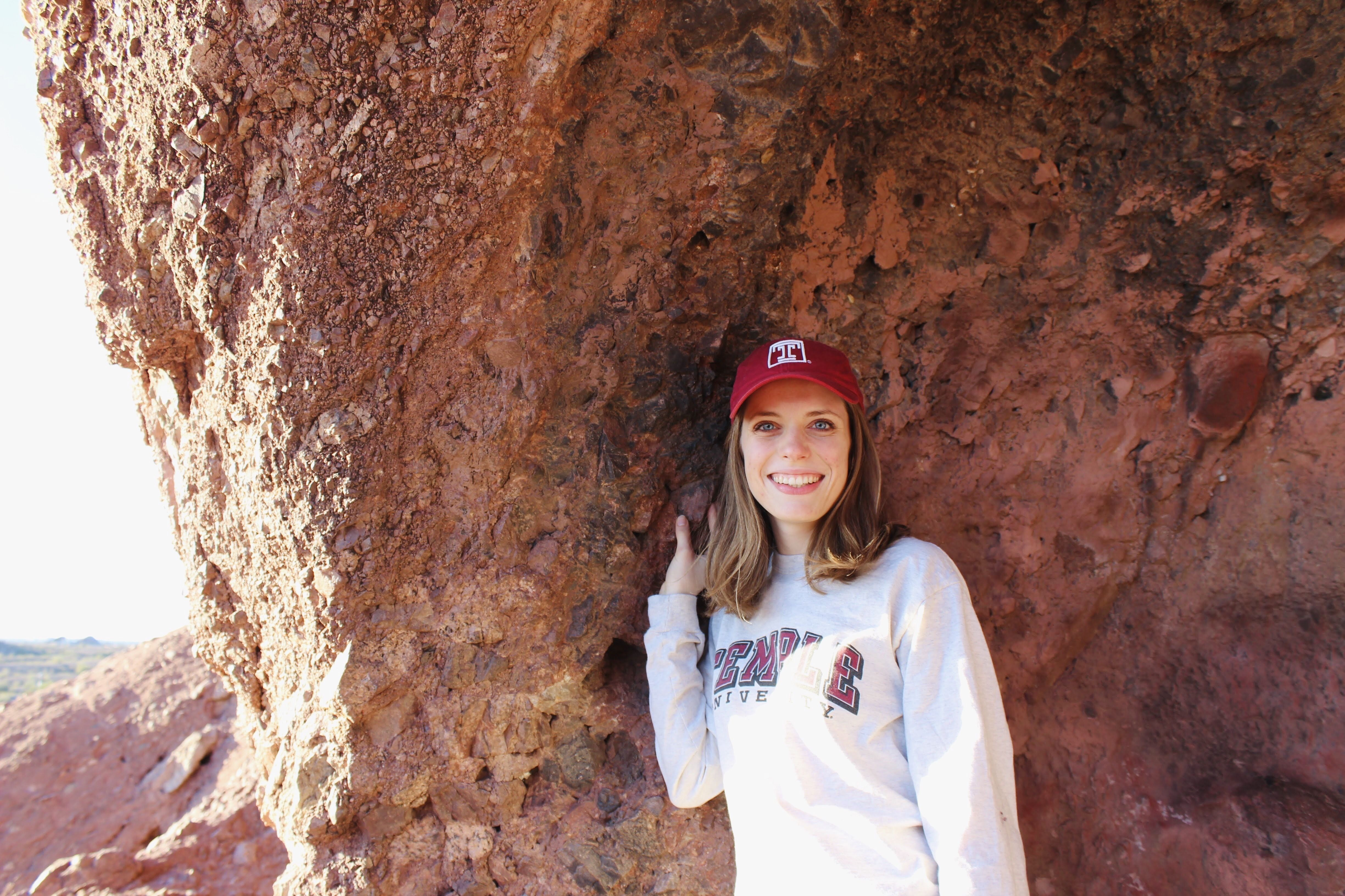 A College of Science and Technology student poses in front of a big rock.