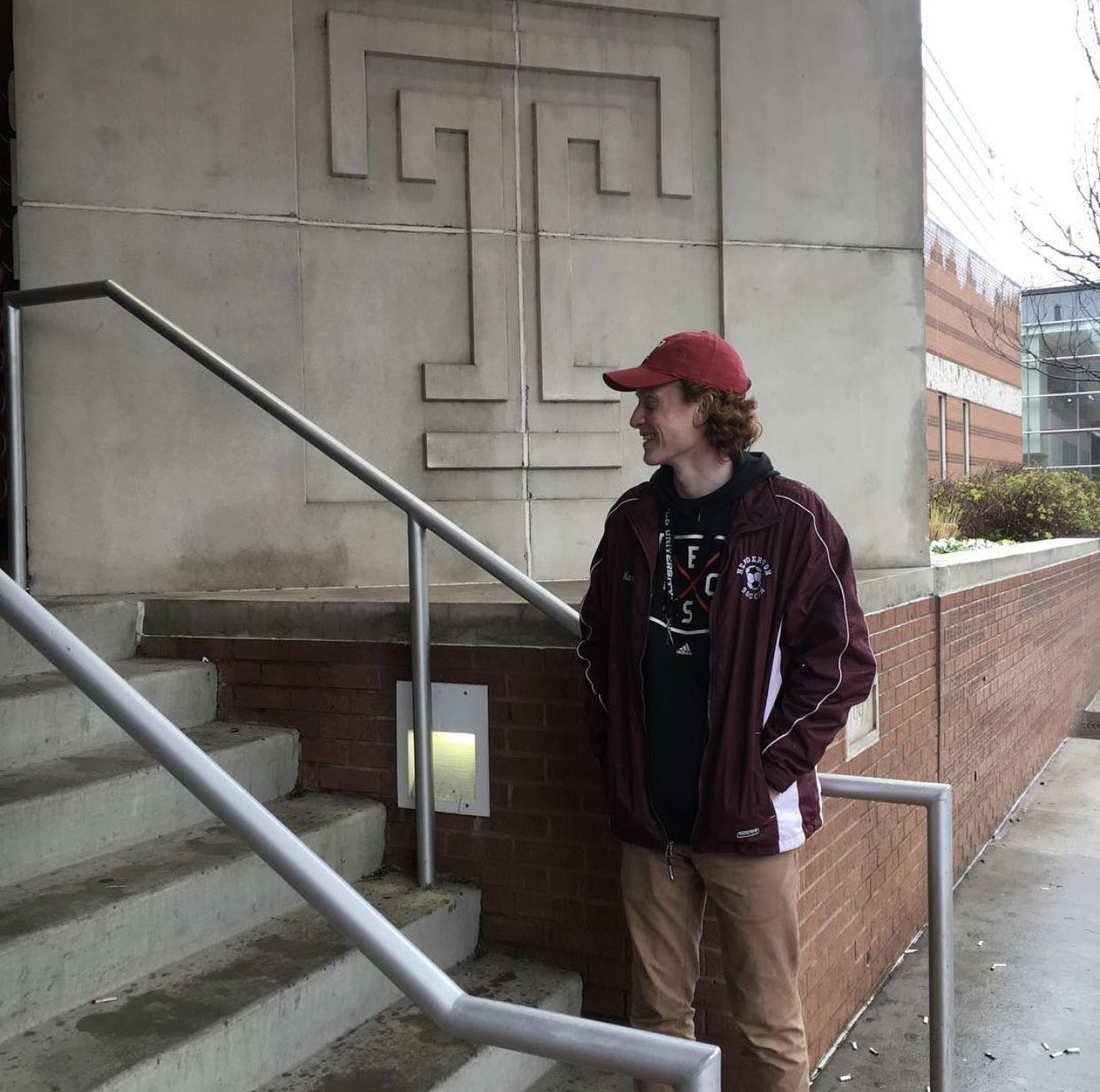 A College of Science and Technology student stands outside a building on campus.