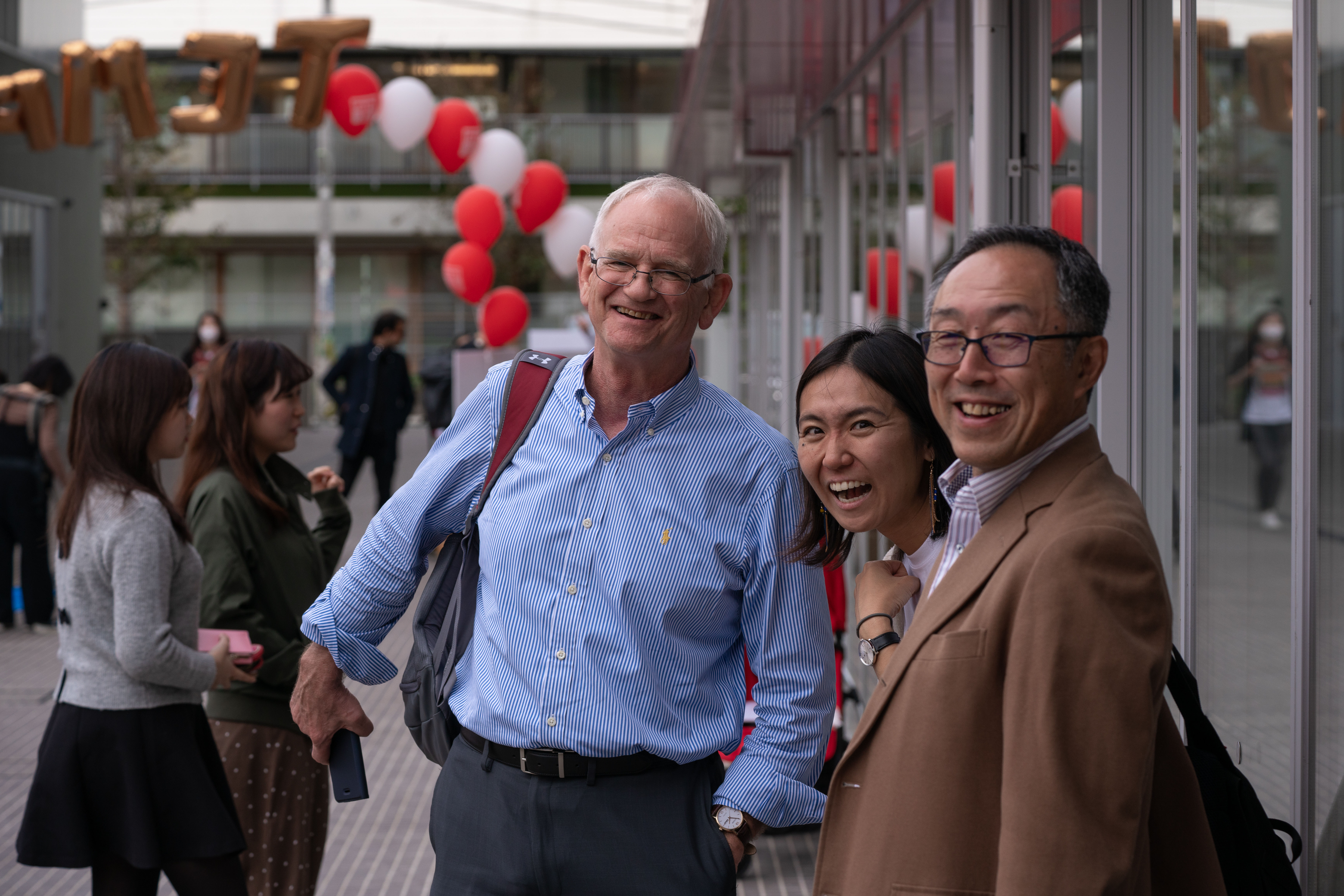 The dean of Temple University Japan poses with two other people.