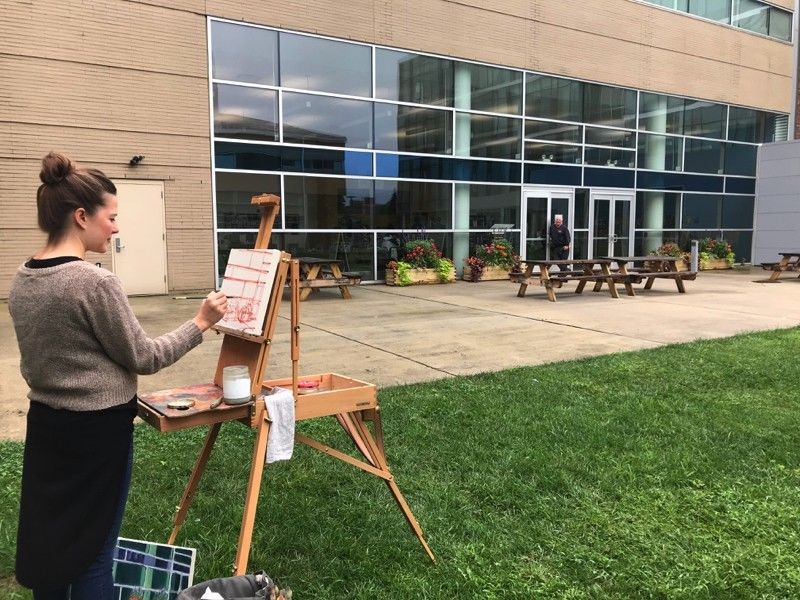 A student paints in the courtyard at Tyler.
