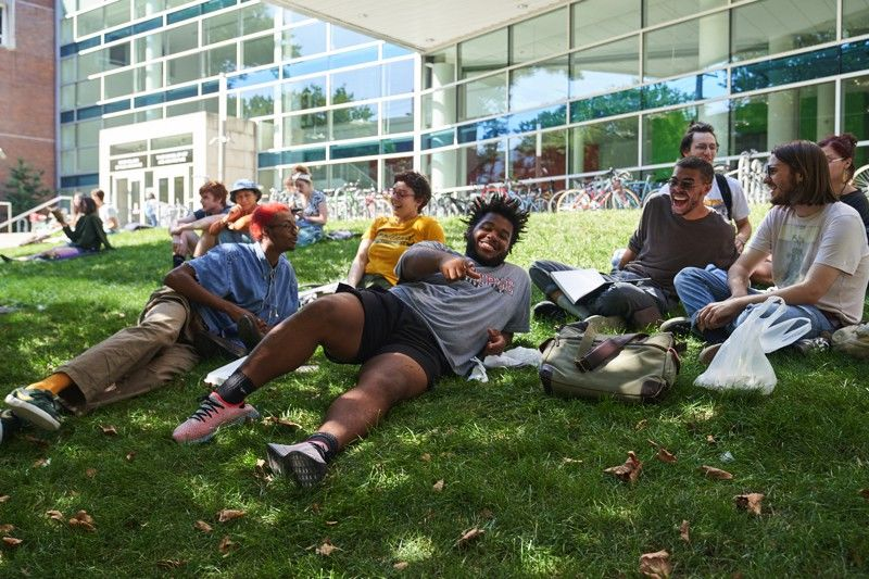 Students relaxing on the front lawn of the Tyler School of Art and Architecture.