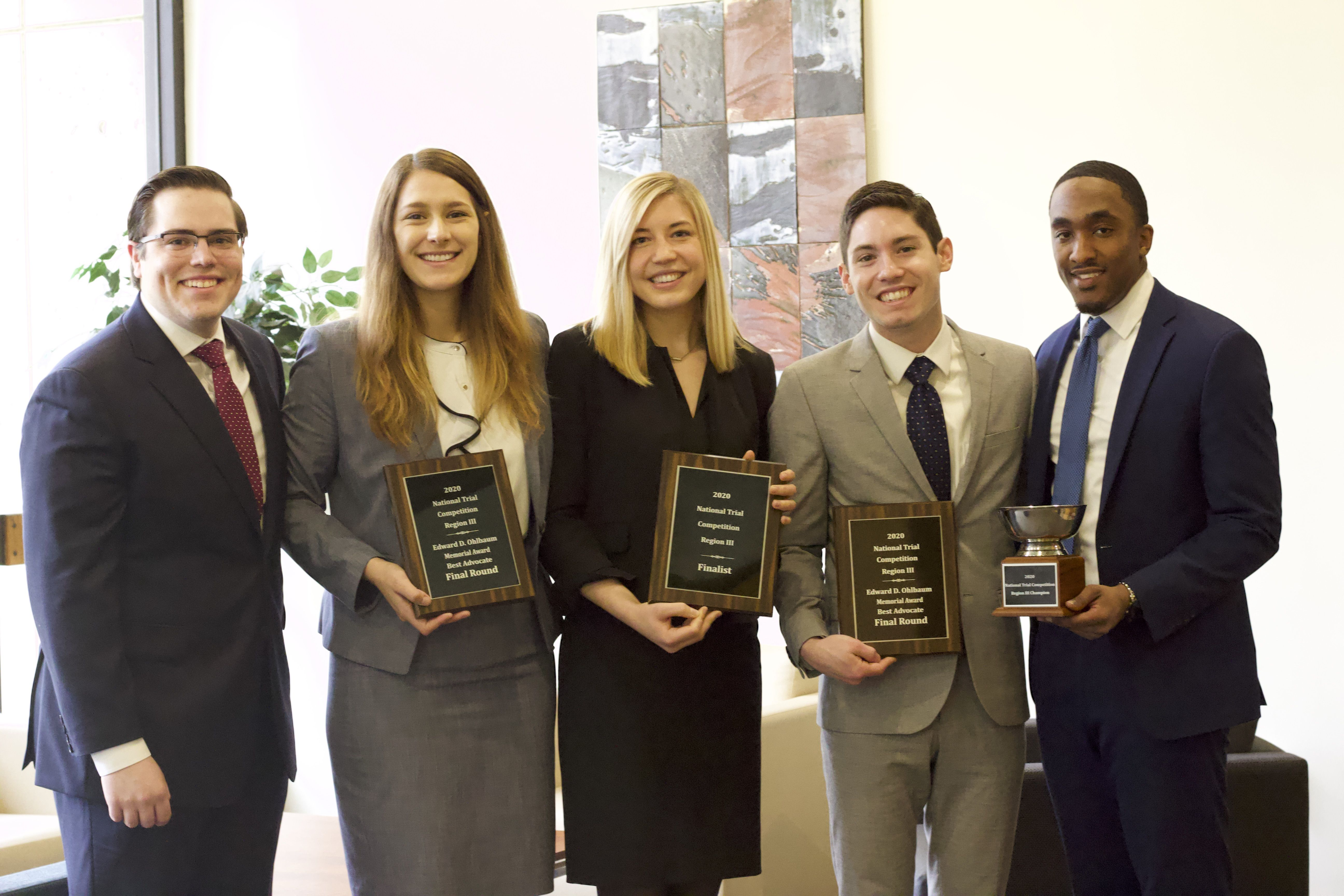 The 2020 Temple Law National Trial Team shows off some hardware after their commanding performances in the Regional III Championships of the National Trial Competition.