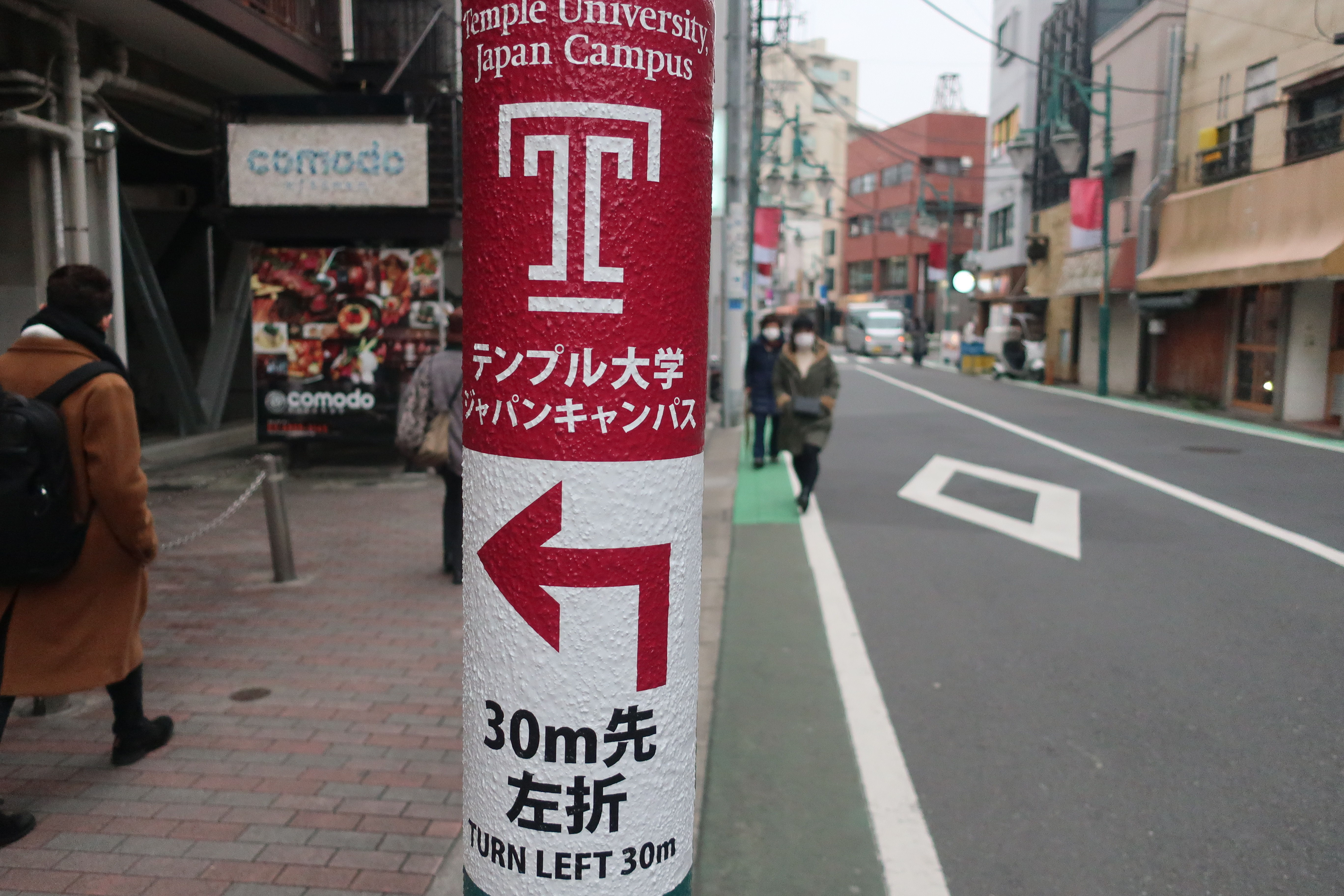 A sign on a street in Tokyo directing towards Temple University Japan.