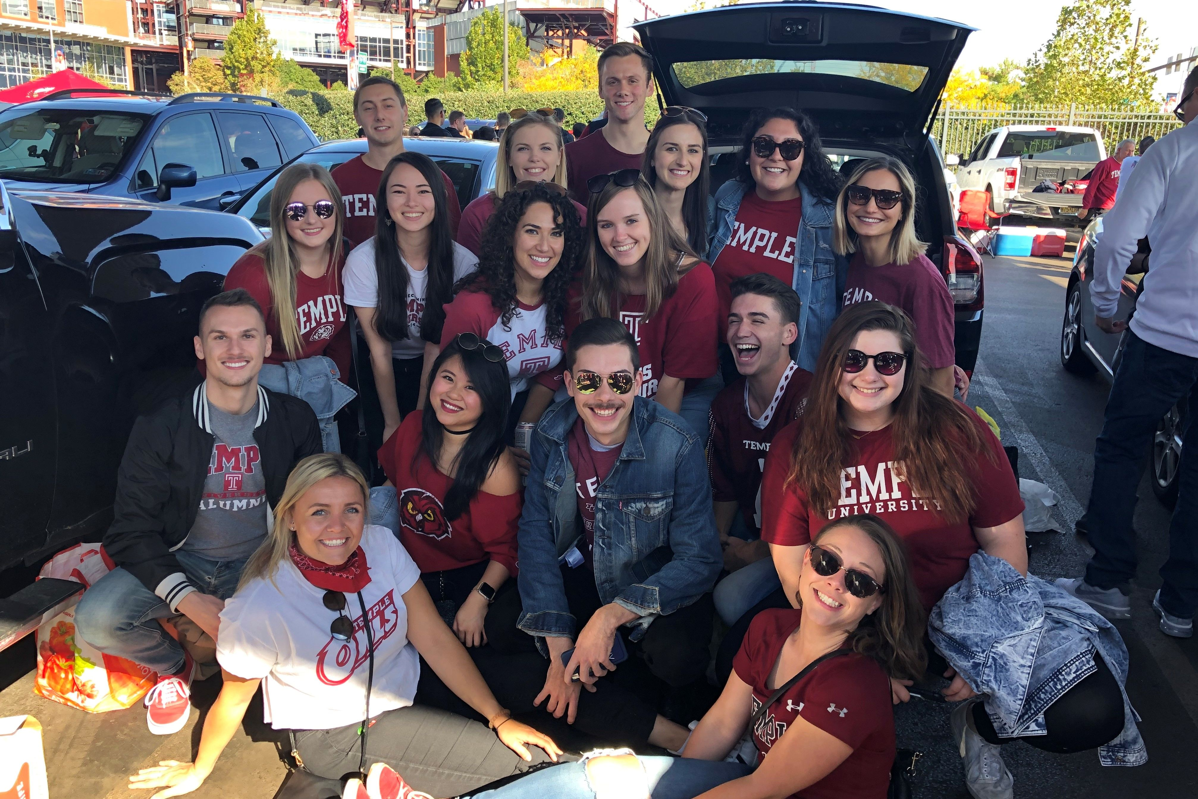 A group of revelers join Tabitha Miller at the Alumni Tailgate.