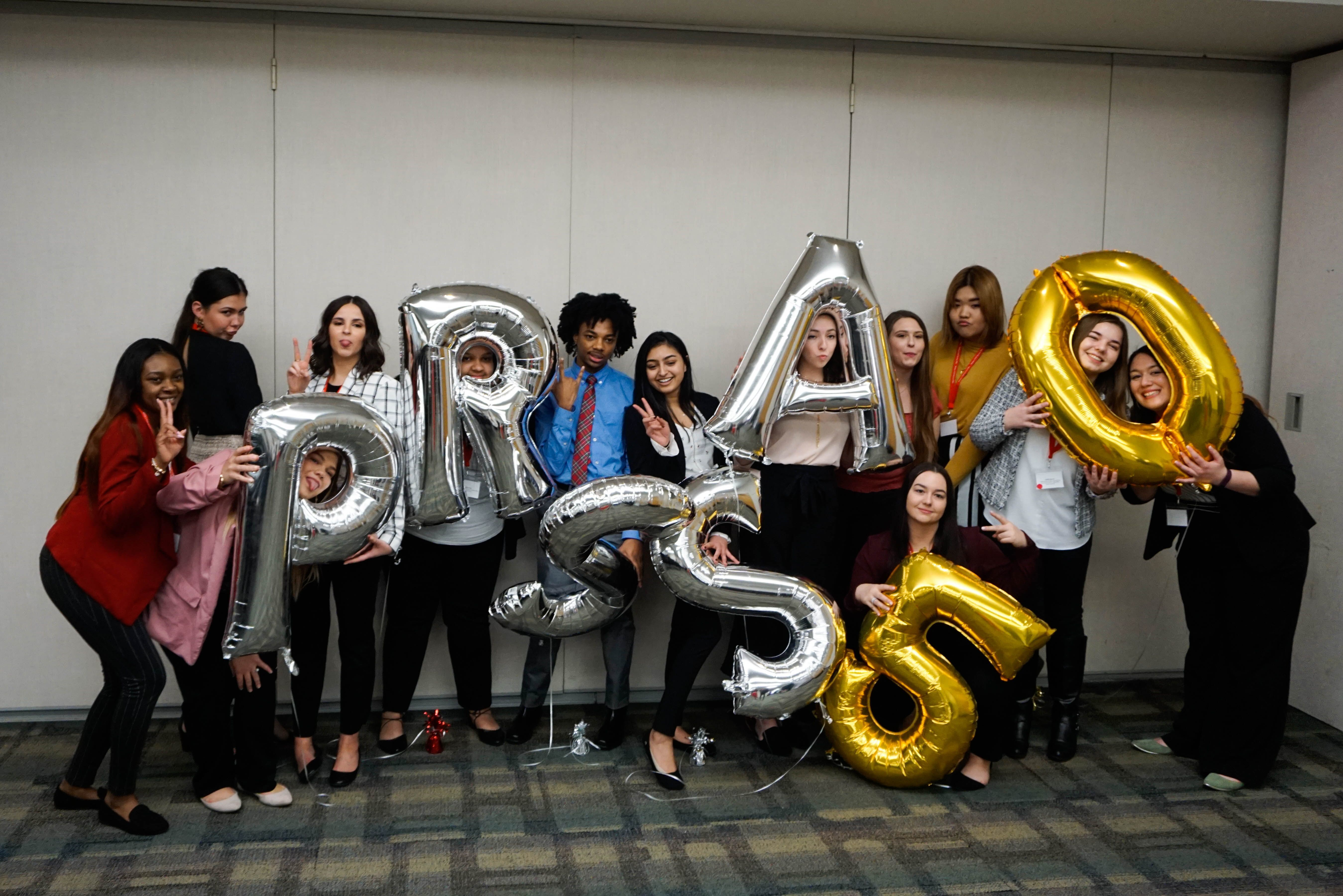 Students from the Klein College of Media and Communication pose with large letter and number balloons.