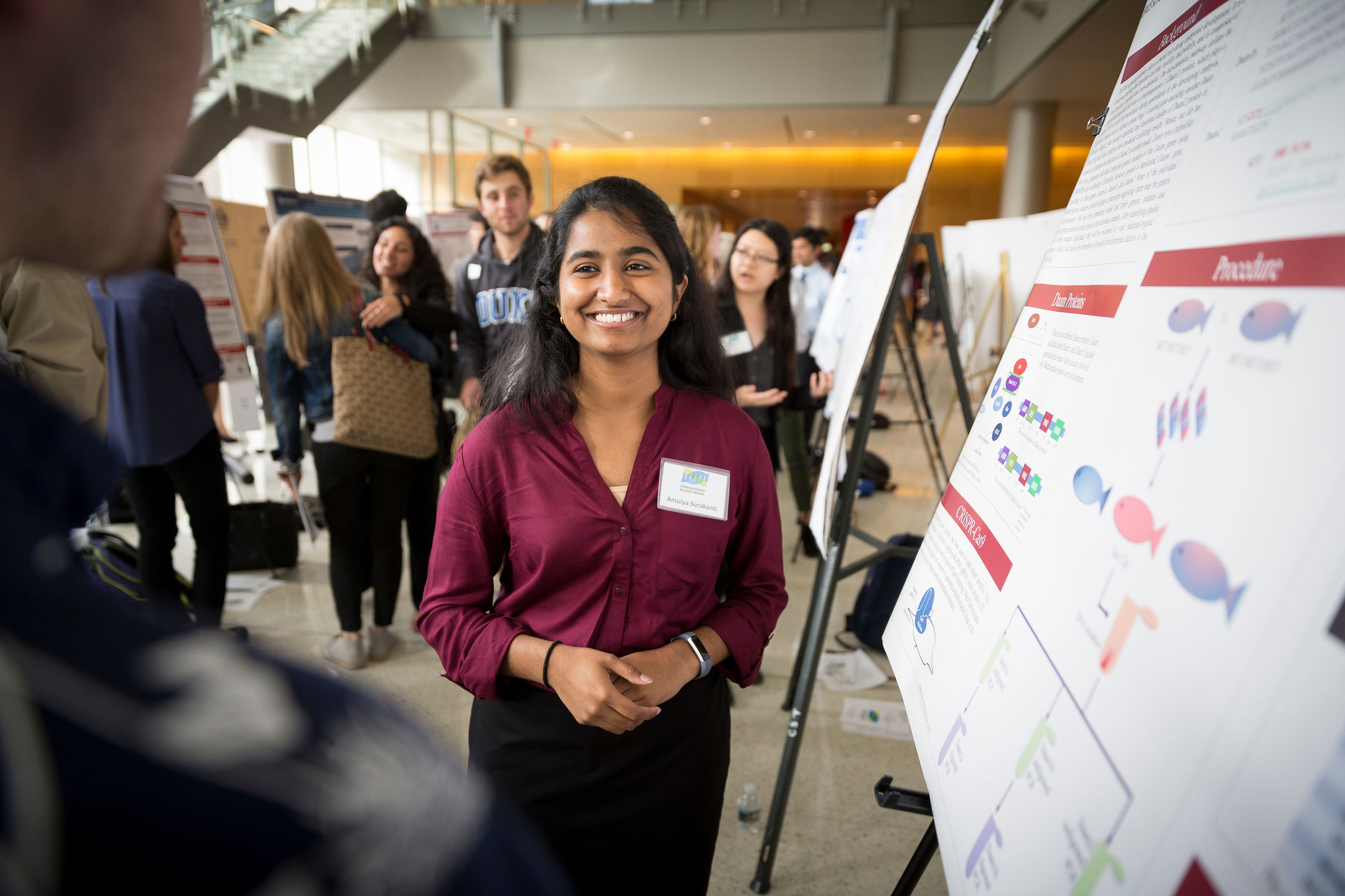 A College of Science and Technology student standing in front of her poster during an industry conference.