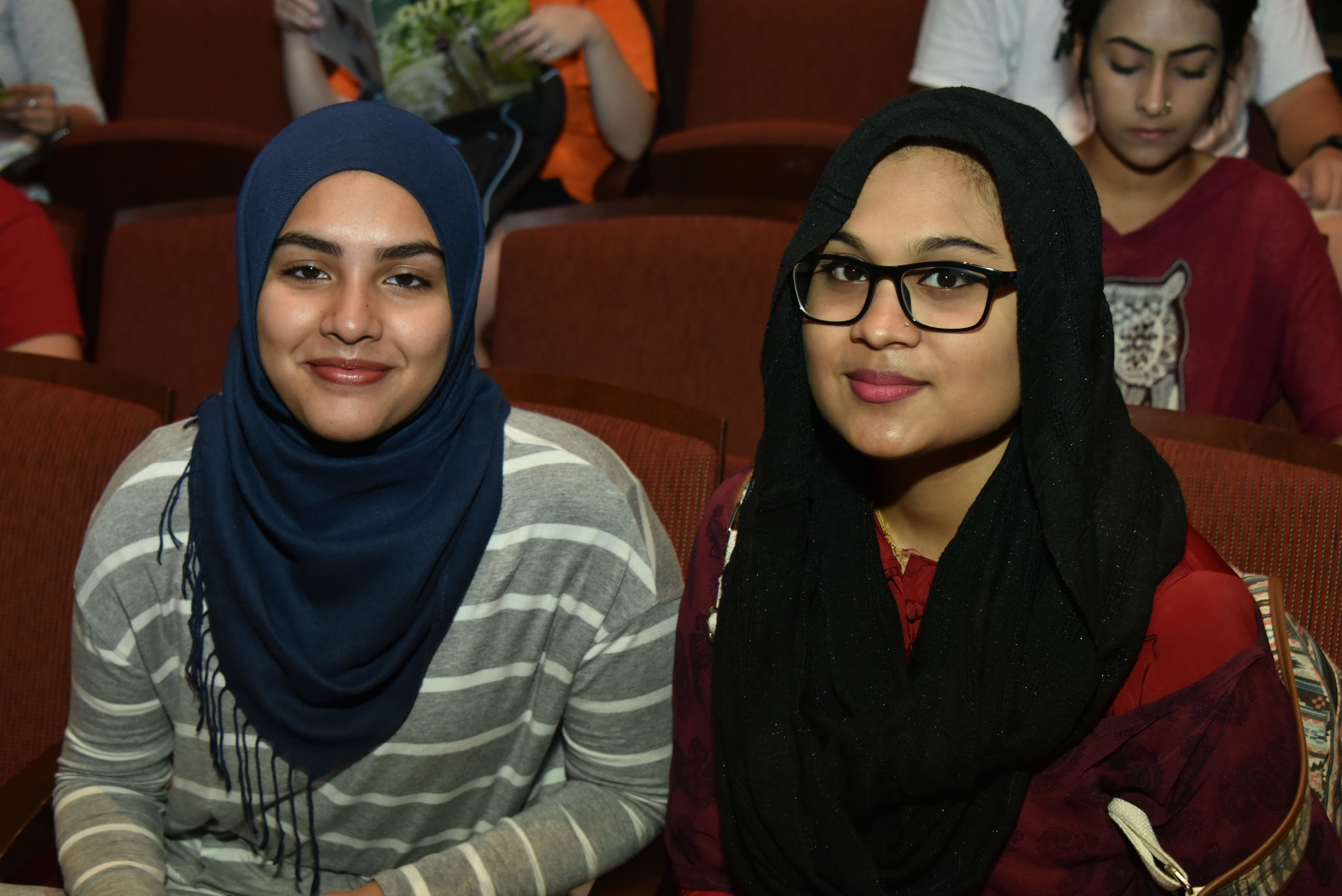 Two College of Science and Technology students sit together in a lecture hall.