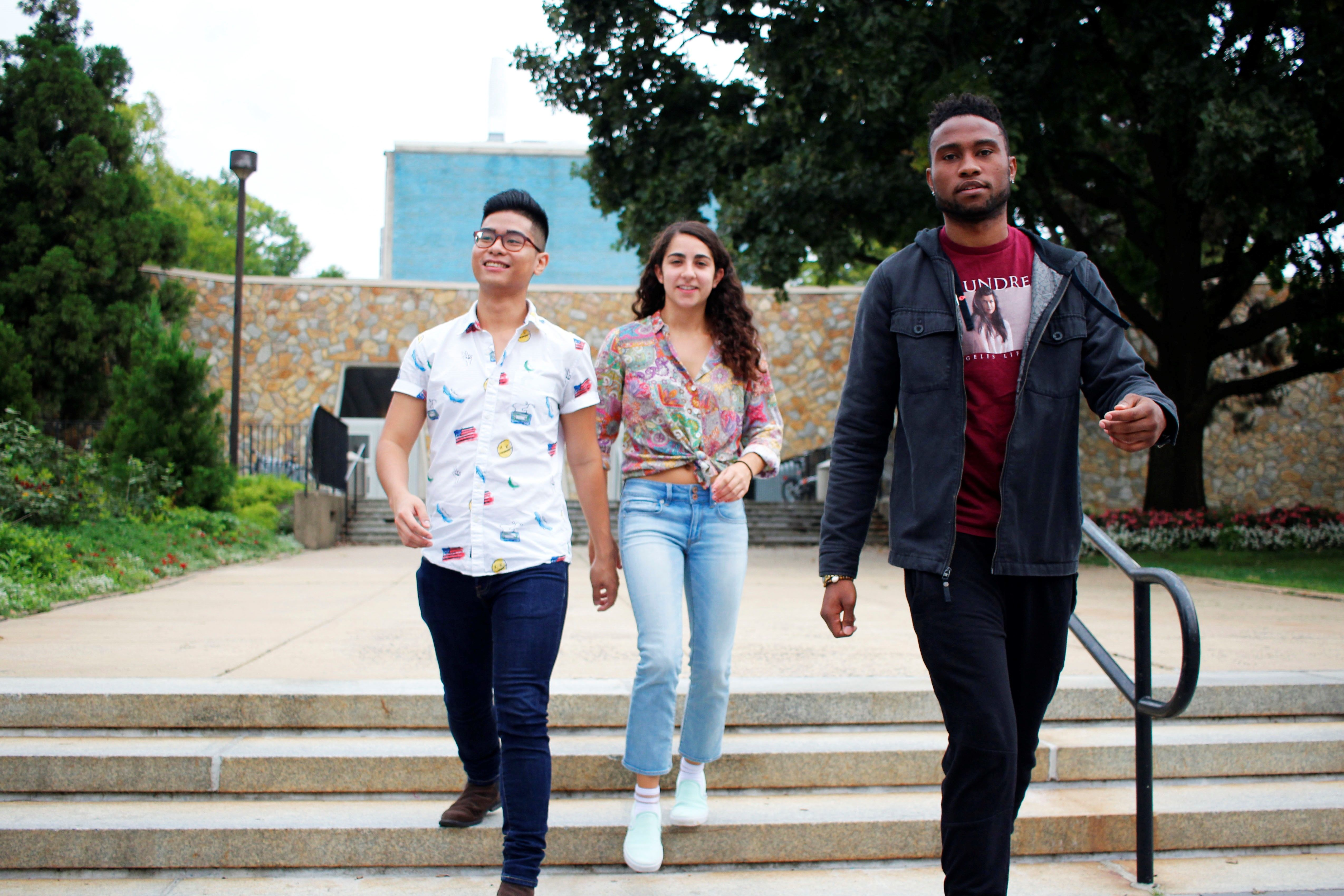 Three students walk down steps together on campus.